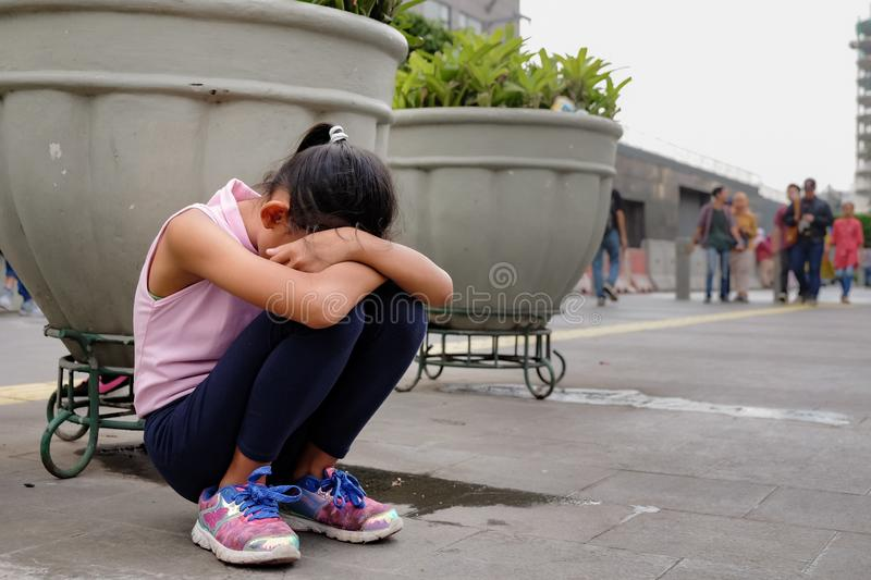 Lost Asian Little Girl Sitting Sad and Lonely On The City Pedestrian Seems Lost or Crying stock photos