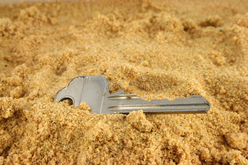 Lost on the Beach 2. A key lost on the beach and half buried in the sand royalty free stock image