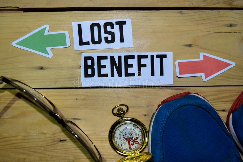Lost or Benefit opposite direction signs with sneakers, eyeglasses and compass on wooden. Vintage background. Business, education and finance concepts stock images