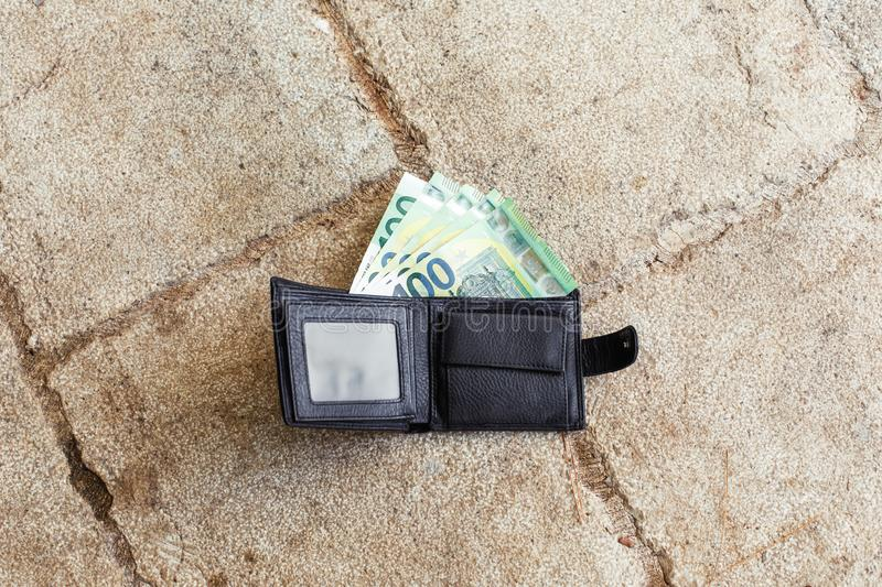 Lost black leather wallet with money euro on street stock photo