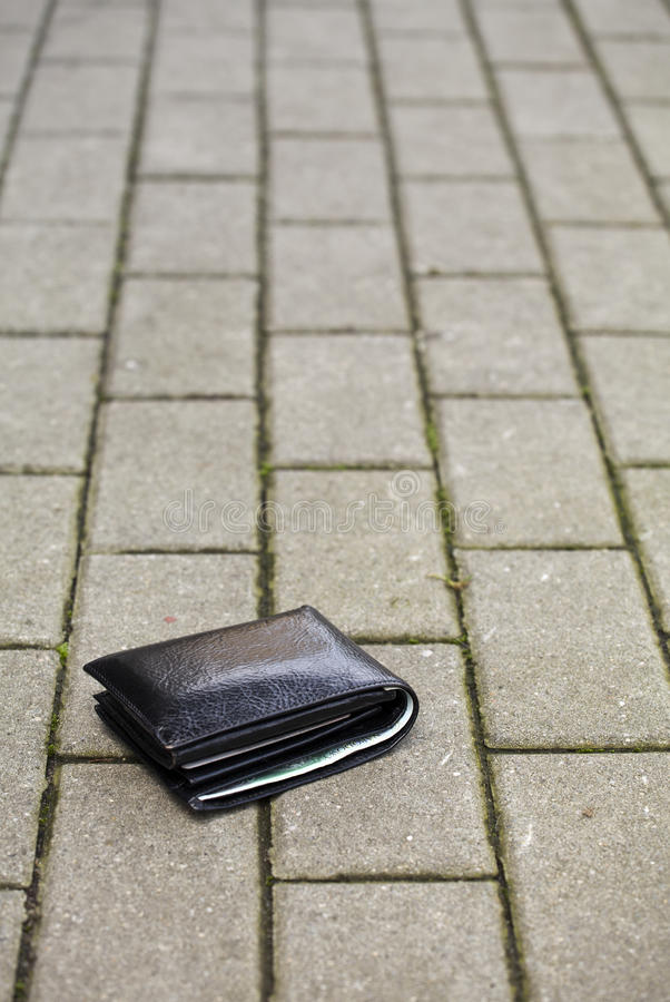Lost black wallet. Lost black leather wallet with money lost at sidewalk royalty free stock image
