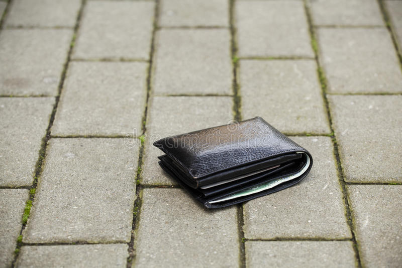 Lost black wallet. Lost black leather wallet with money lost at sidewalk royalty free stock photo