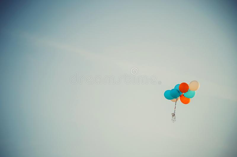 Lost bunch of painted balloons in a blue sky flying away with empty space for text.  stock images