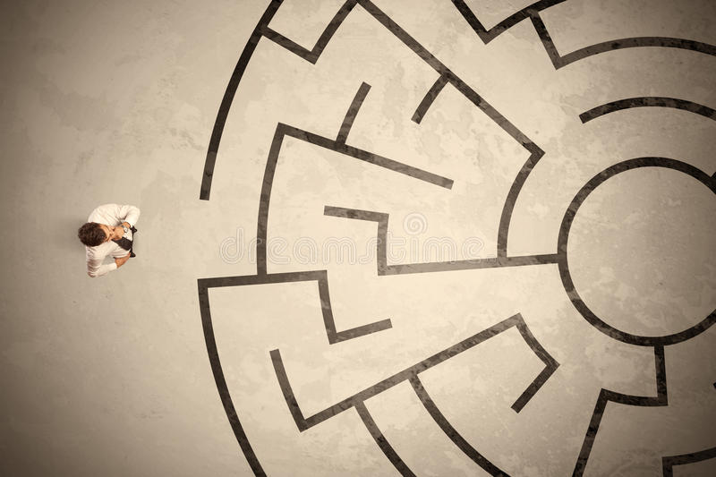 Lost business man looking for a way in circular labyrinth. Concept stock photography