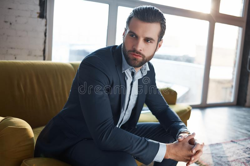 Lost in business thoughts...Thoughtful handsome young businessman is thinking about business while sitting on the sofa royalty free stock images