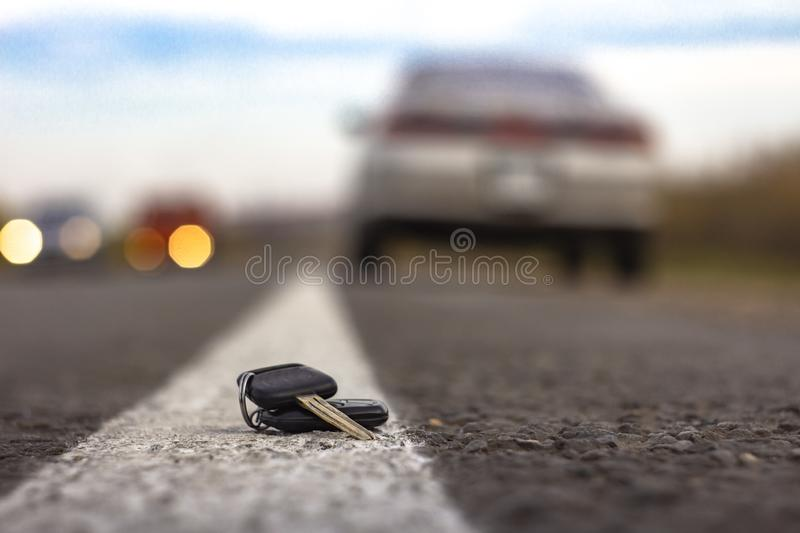 Lost car keys lying on the roadway, on a blurred background with bokeh effect stock photos