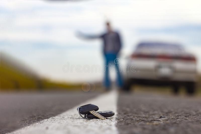 Lost car keys lying on the roadway, on a blurred background with bokeh effect royalty free stock photography