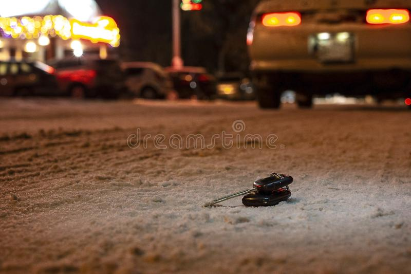 Lost car keys on the road powdered with the first snow at night. on blurred background royalty free stock images