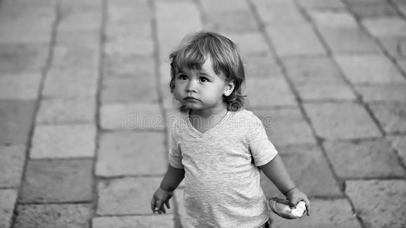Lost child. Portrait of blond hazel-eyed kid. Lost child. Photo portrait of cute fair-haired blond hazel-eyed kid little child baby boy wearing vest holding bun stock image