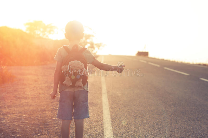 Lost child. Standing on the road hitchhiking on a sunset stock photos