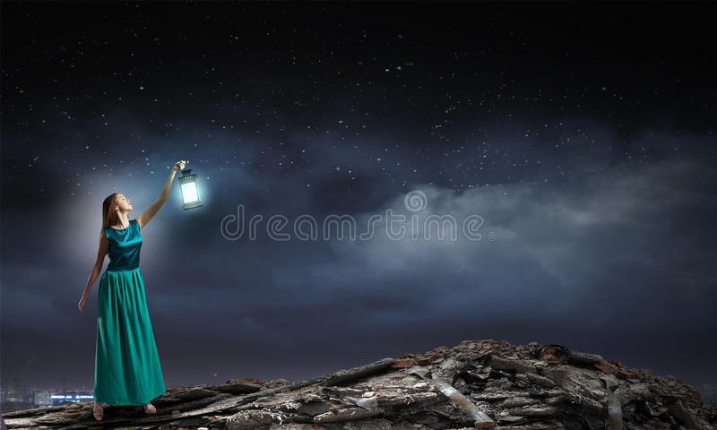 Lost in darkness. Young woman in green dress with lantern walking in darkness royalty free stock photos