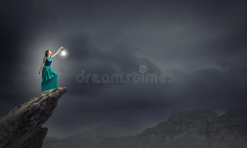 Lost in darkness. Young woman in green dress with lantern walking in darkness royalty free stock photography