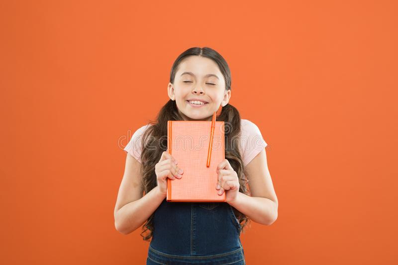 Lost in fairytale. literature lesson. back to school. writing notes. kid diary. school girl read book on orange royalty free stock images