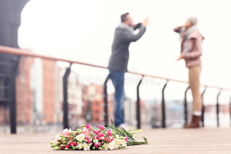 Lost flowers and arguing couple royalty free stock photography