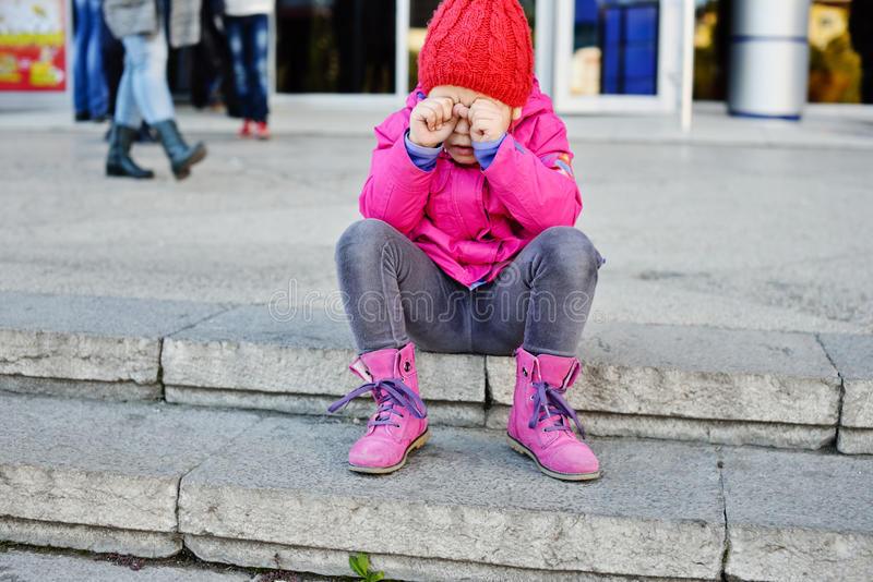 Lost girl. In the city sitting and crying royalty free stock photography