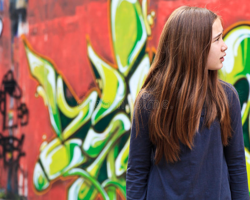 Lost girl by a graffiti wall. Girl looking lost and lonely in front of a graffiti wall royalty free stock photos
