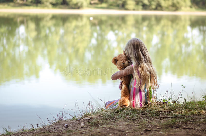 Lost girl by the pond hugging her teddy bear. Little kid with teddy bear sitting by the lake alone royalty free stock image