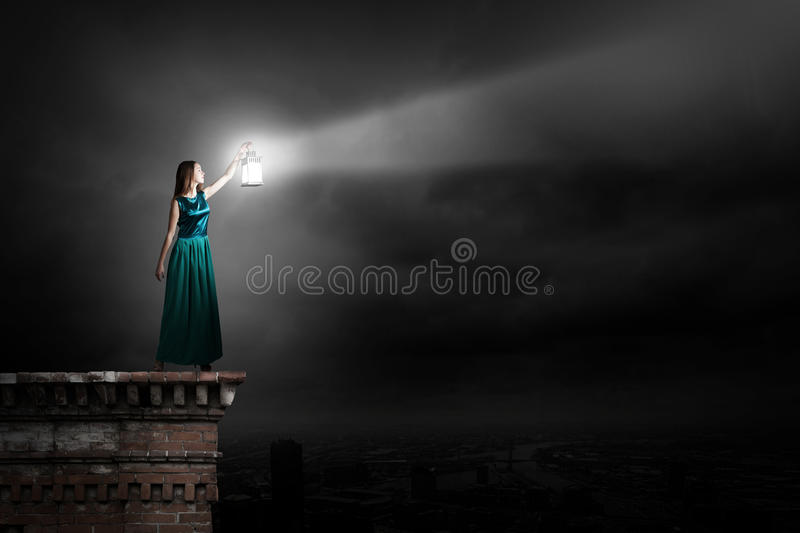 Lost on her way!. Young woman in green dress with lantern in darkness stock images