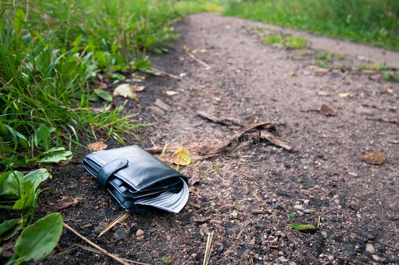 Lost leather wallet with money drop on sidewalk , lost money concept. Copy space on top stock photography