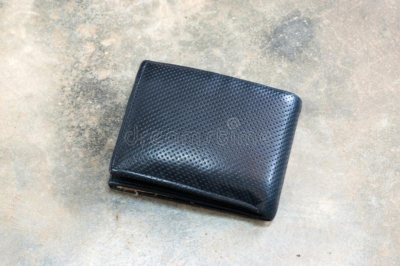 Lost leather wallet with money on the floor. Close-up of wallet lying on concrete background stock photo