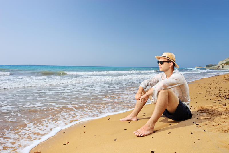 Lost male tourist sitting on a beach and thinking stock photos
