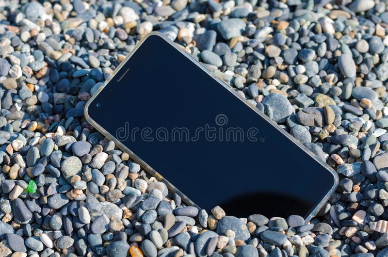 Lost mobile phone on the beach among the sea small pebbles. The lost mobile phone is on the beach among small sea pebbles of different shades of color in the stock images