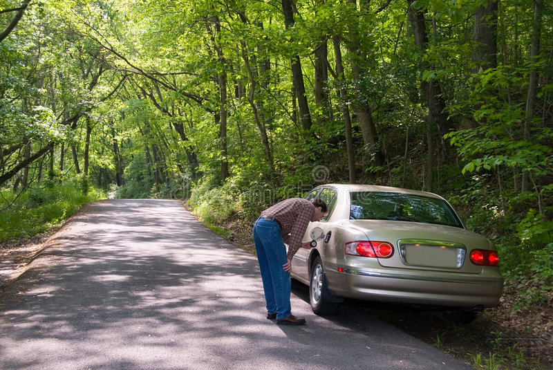 Lost No Gas. A man looking into his gas tank. He's lost, on a country road and has run out of gasoline in his car stock photography