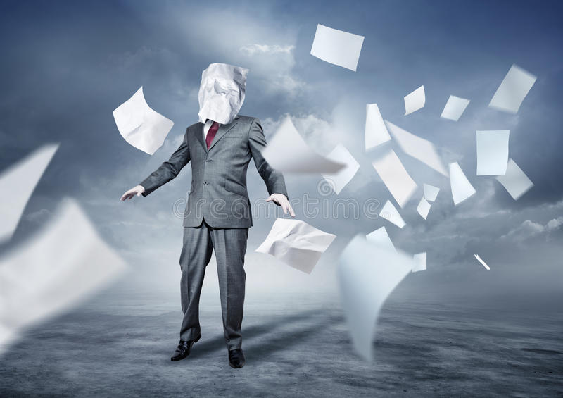 Lost In Paperwork. A businessman's face covered in paperwork. Business concept