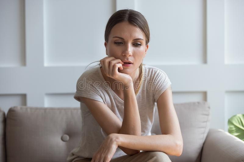 Lost on sad thoughts woman sitting on couch at home stock photography