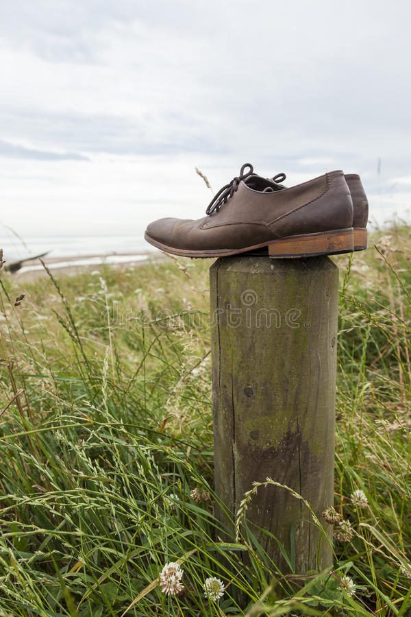 Lost shoes. Pair of mens brown leather shoes lost or discarded and left on wooden post at coastal site royalty free stock photography