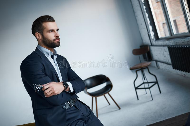Lost in thoughts. Well Dressed businessman in stylish suit is looking aside thoughtfully in a modern office stock photo