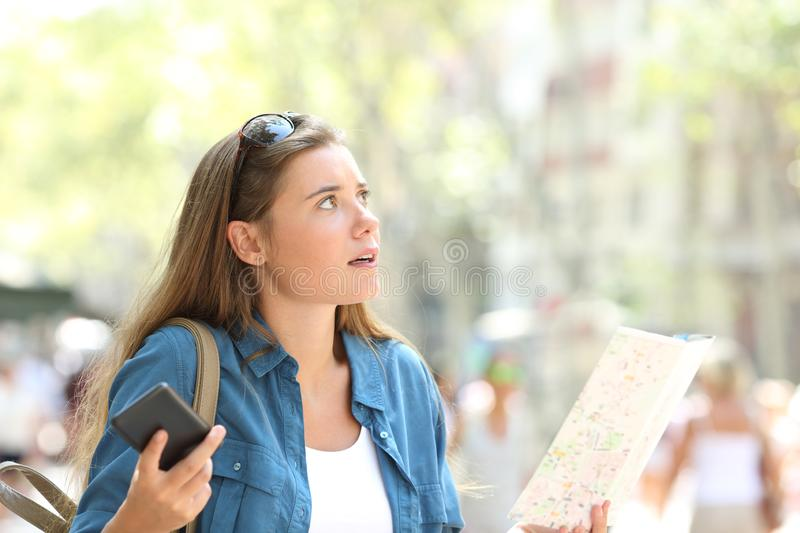 Lost tourist trying to find location in the street. Lost tourist trying to find location holding phone and paper map in the street stock photos