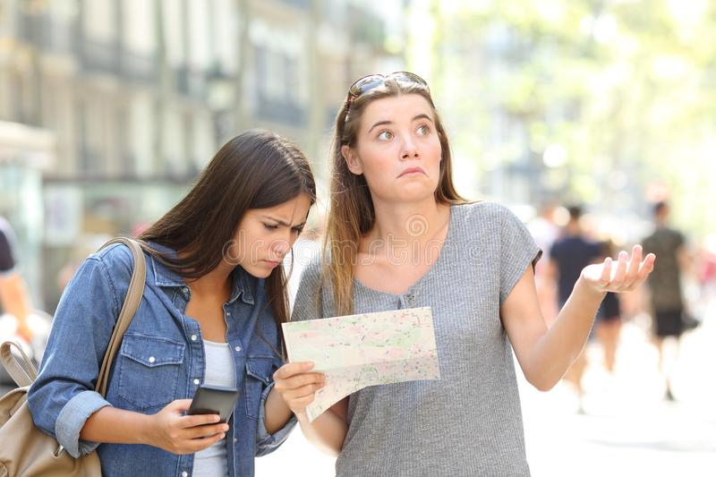Lost tourists consulting map and phone. Two lost tourists consulting a paper map and a smart phone searching location in the street royalty free stock image
