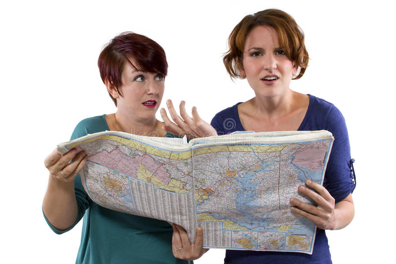 Lost Tourists. Two young women are lost and looking at a map royalty free stock photo