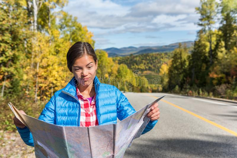 Lost travel tourist woman searching for directions on map on road trip in nature fall autumn outdoors. Funny Asian girl making royalty free stock photos