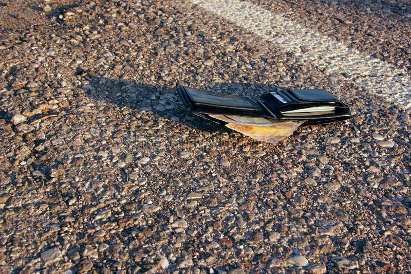 Lost wallet. At the edge of a asphalted road stock image