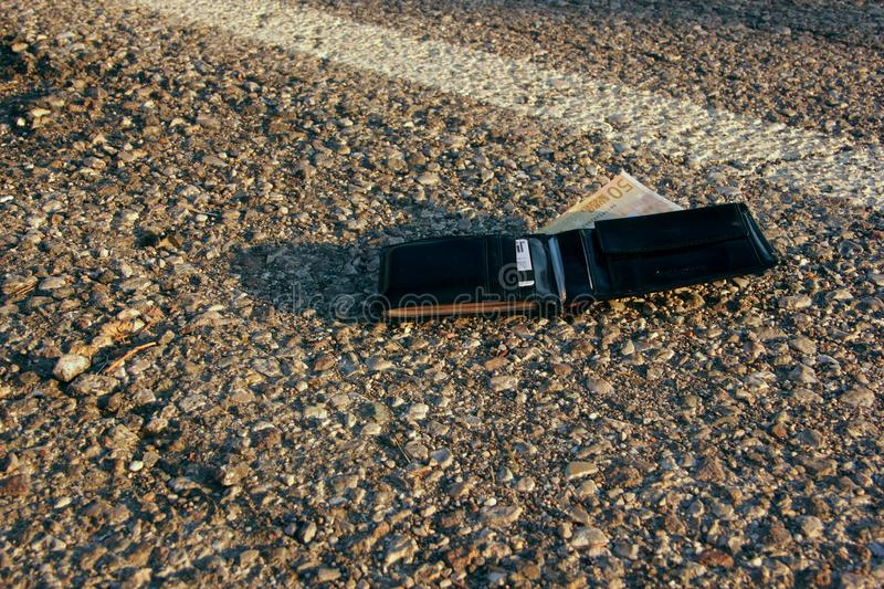 Lost wallet. At the edge of a asphalted road stock photography