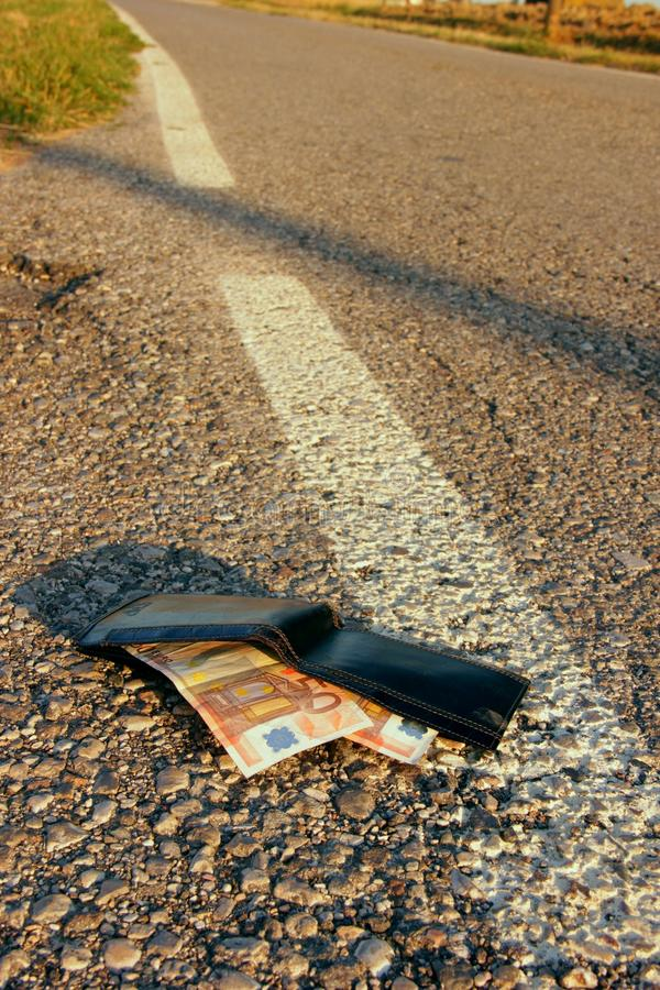 Lost wallet. At the edge of a asphalted road royalty free stock photography
