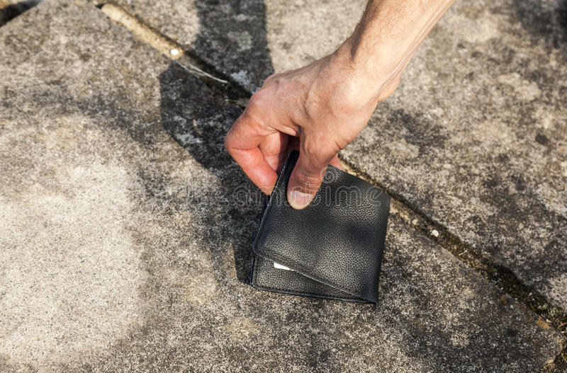 Lost Wallet. Person picking up a leather wallet from the ground royalty free stock photography