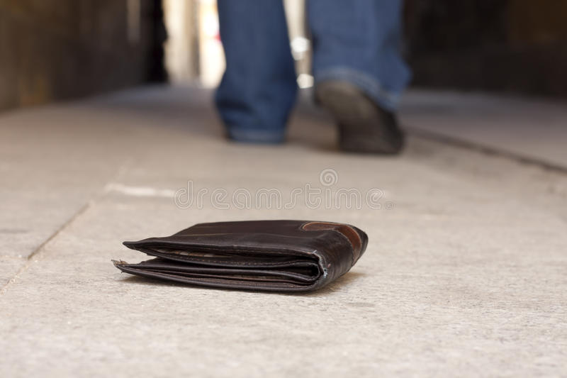 Lost wallet on the street and legs of the walking man. Concept royalty free stock image