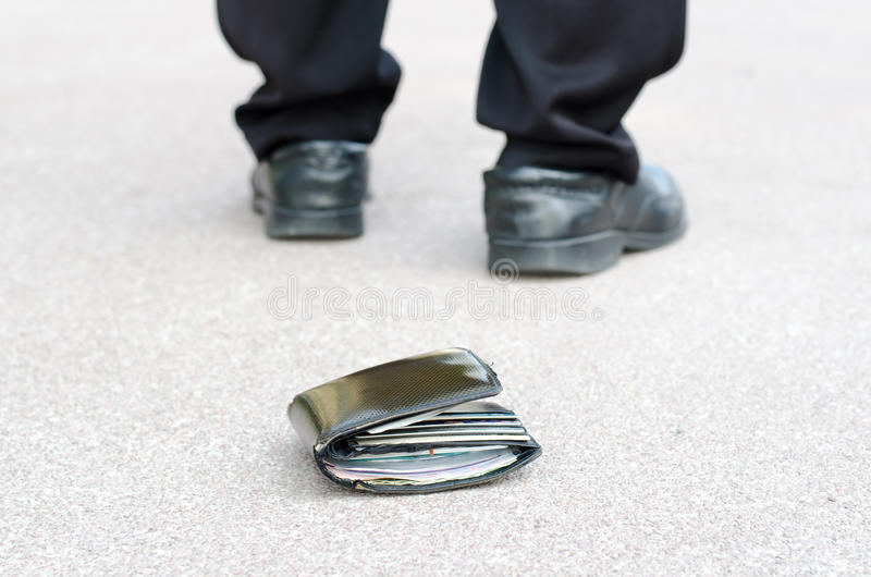 Lost wallet on the street and legs of the walking man. Lost wallet on the street in the park and legs of the walking man concept royalty free stock photography