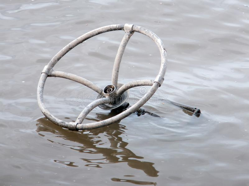 Lost Wheel. Old metal steering wheel, abandoned and submerged in the Mississippi River stock photography