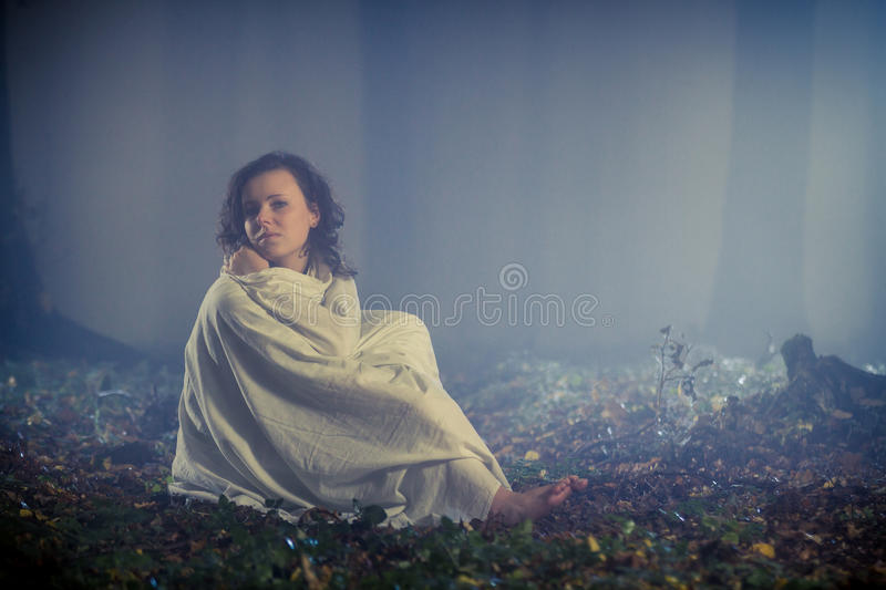 Lost woman with white sheet in dark forest stock photography