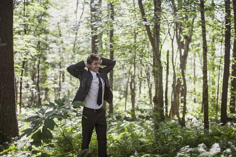 Lost man. A young man wearing a suit lost and confused in a forest stock image