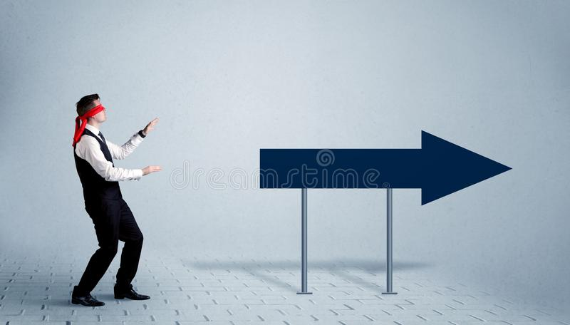 Businessman with blindfolds. A lost young sales person with blindfolds trying to find the right path concept with large blue arrow sign pointing forward royalty free stock images