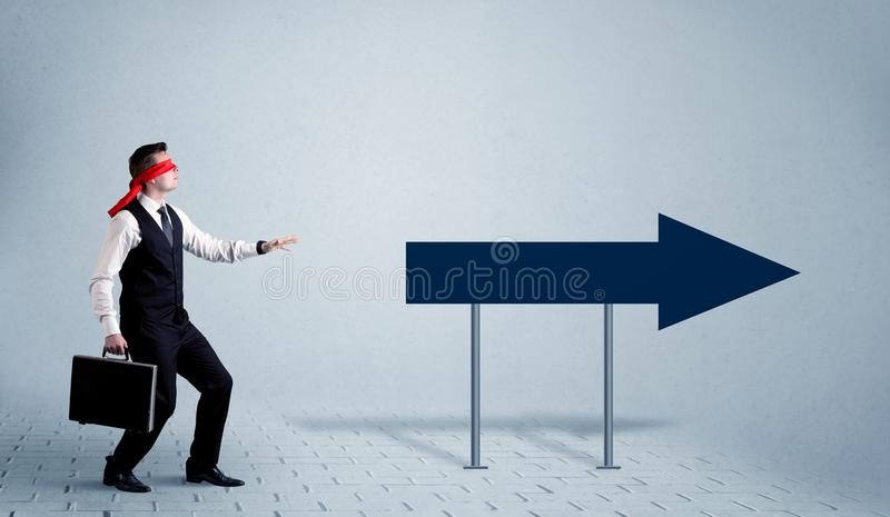 Businessman with blindfolds. A lost young sales person with blindfolds trying to find the right path concept with large blue arrow sign pointing forward stock photos
