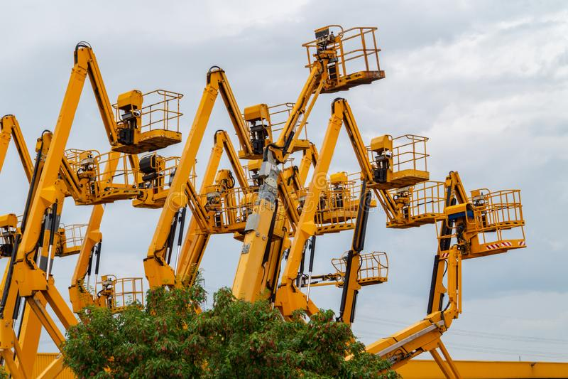 Lot of aerial work platforms. Articulating boom lifts. Construction equipment royalty free stock images