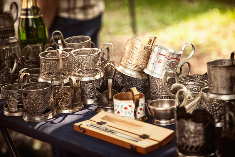 Lot of antique metal glass holders at a flea market. Many old ornate cup holders at a garage sale stock images