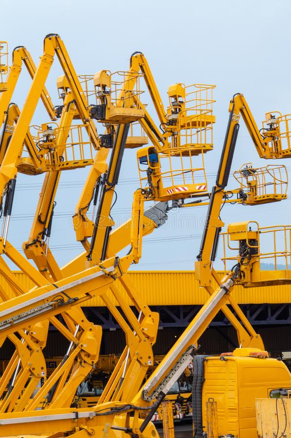 Lot of articulating boom lifts. Construction equipment manufacturing royalty free stock photos