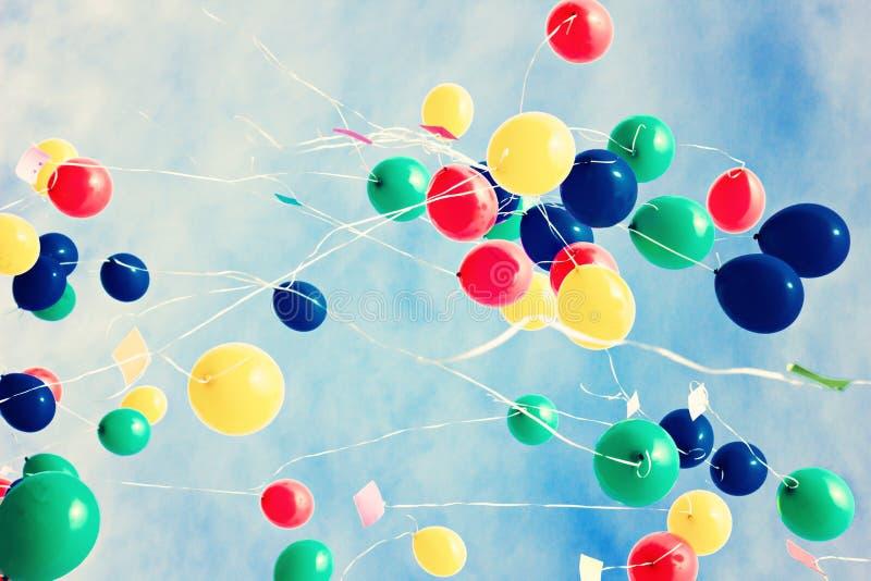 A lot of balloons over a retro sky. Various colorful balloons flying in over a retro sky stock image
